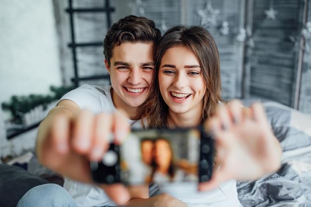 Paare, die im bett sich entspannen und ein selfie nehmen