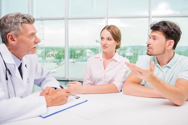 Paare, die im büro sitzen und mit praktiker sprechen.