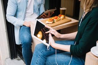 Paare, die im Café sitzen und Tabletten verwenden
