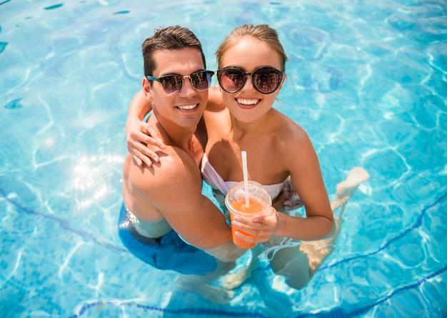 Paare, die im erholungsort sich entspannen und cocktails trinken.