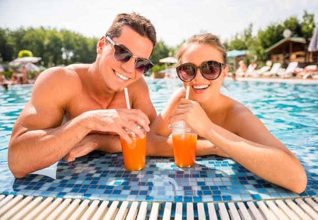 Paare, die im erholungsortpool, trinkende cocktails sich entspannen.