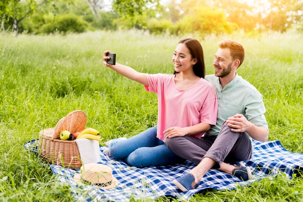 Paare, die im park sitzen und selfie nehmen