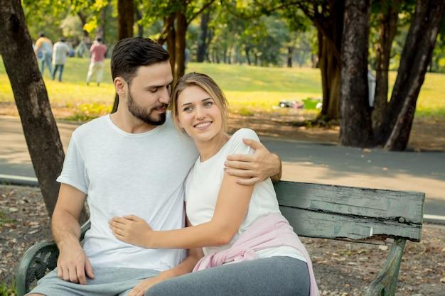 Paare, die im park sitzen und umarmen.