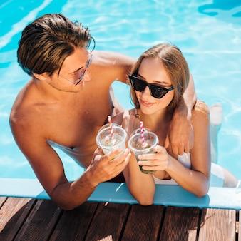 Paare, die im pool glücklich sind