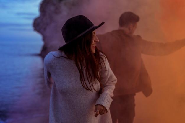 Paare, die im rauch auf seeufer stehen
