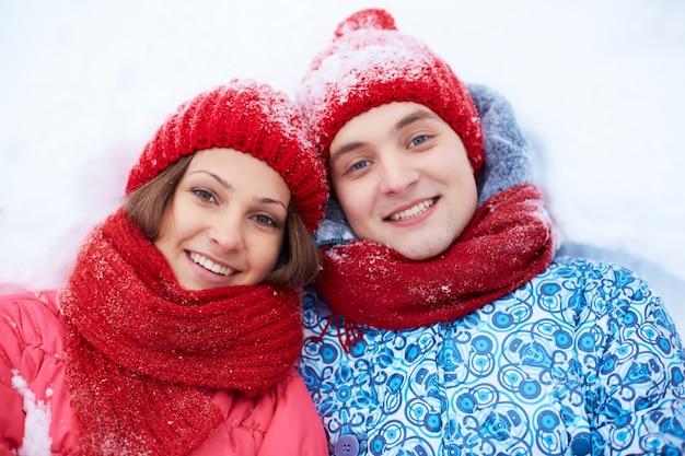 Paare, die im schnee liegen