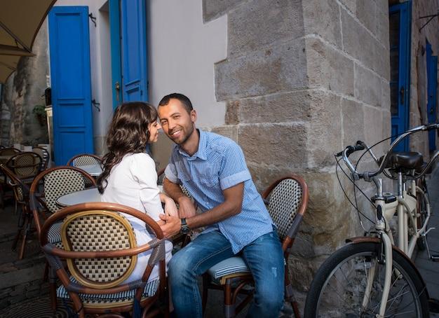 Paare, die im straßencafé nahe ihrem tandemfahrrad sitzen