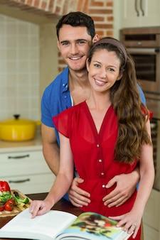 Paare, die in der küche bei der prüfung des rezeptbuches umfassen