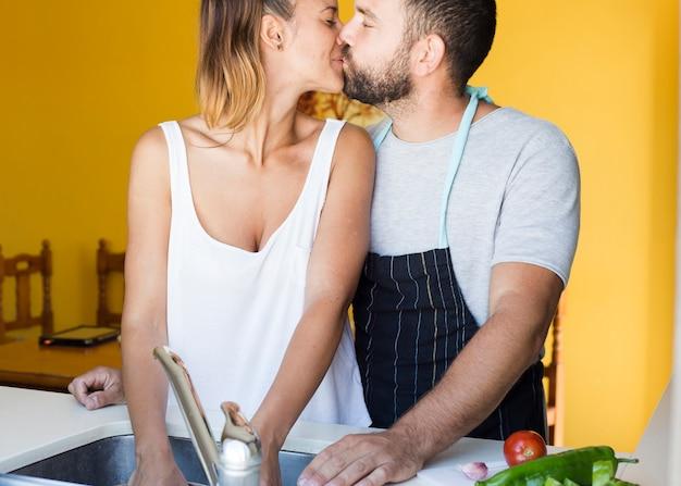 Paare, die in der küche sich küssen