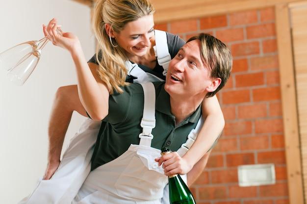 Paare, die in die neue erneuernde wohnung umziehen