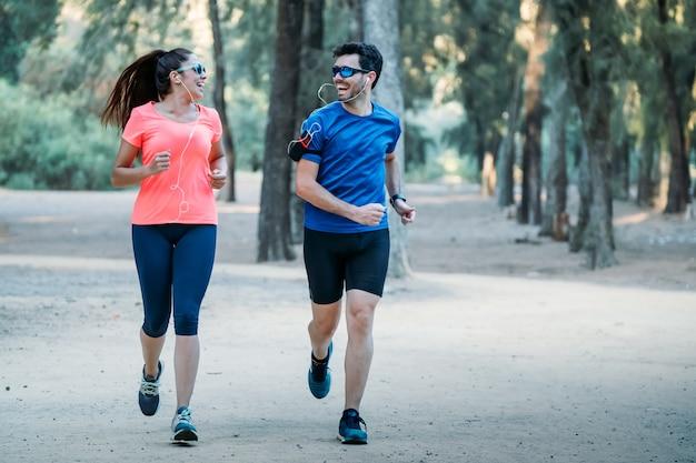 Paare, die in einen park lächelt und musik hört laufen