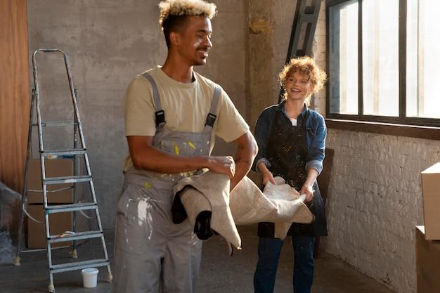 Paare, die in ihrem neuen zuhause gemeinsam einen teppich handhaben