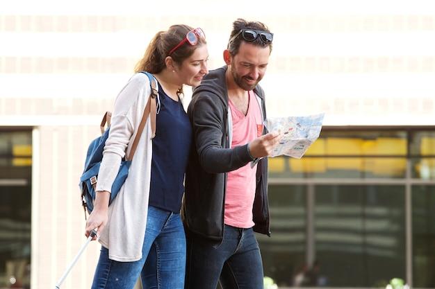 Paare, die in stadt mit den koffern studieren touristische karte gehen