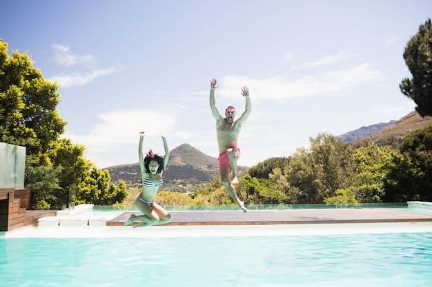 Paare, die in swimmingpool mit ihrer hand angehoben springen