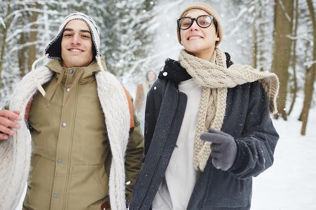 Paare, die in winterwald laufen