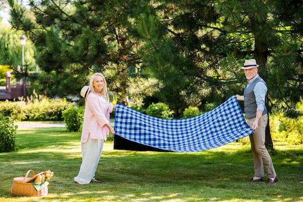 Paare, die kamera beim halten einer decke betrachten