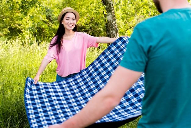 Paare, die kariertes plaid für picknick verbreiten