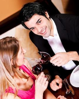 Paare, die klirrende gläser des rotweins trinken
