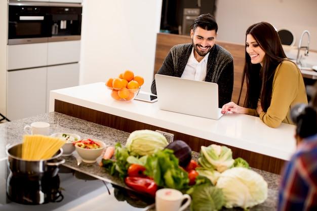 Paare, die laptop in der modernen küche betrachten
