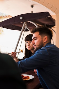 Paare, die lebensmittel im restaurant essen