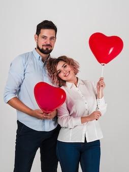 Paare, die mit ballonen für valentinsgrüße aufwerfen