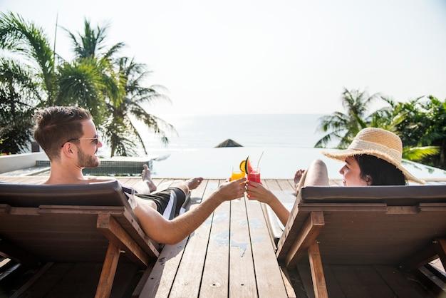 Paare, die mit cocktails am pool anstoßen