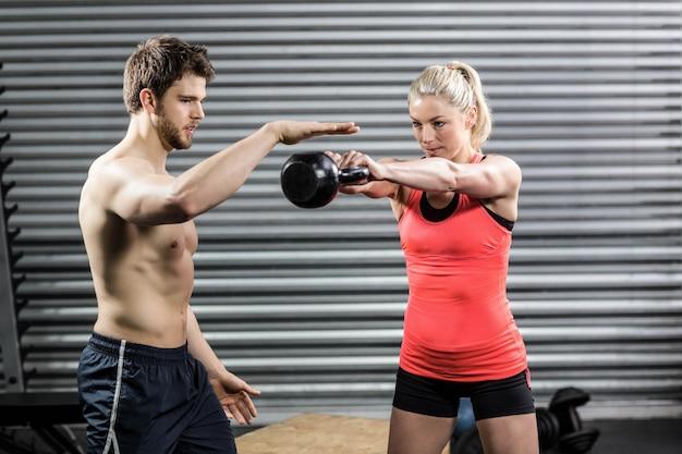Paare, die mit dummköpfen an crossfit turnhalle trainieren