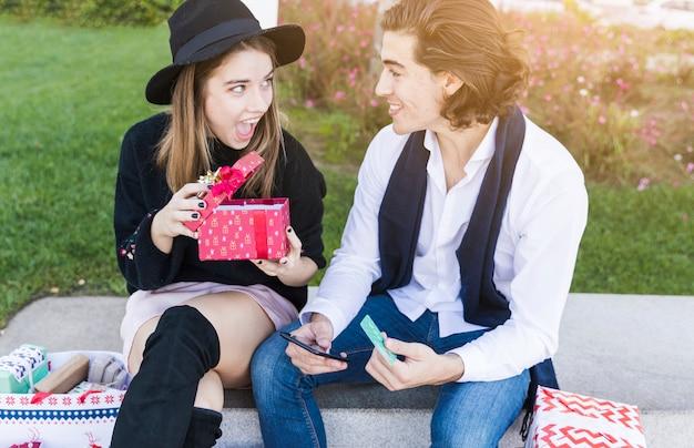 Paare, die mit geschenkbox auf bank sitzen
