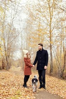 Paare, die mit hund im park und im umarmen gehen