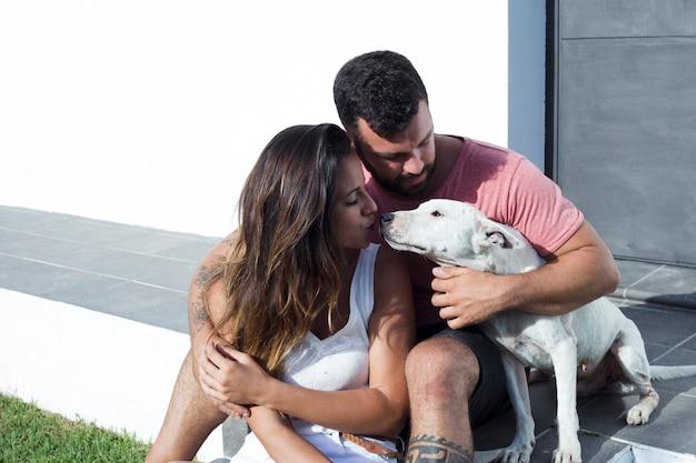 Paare, die mit ihrem hund außerhalb des hauses sitzen