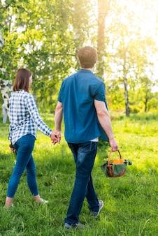 Paare, die mit picknickkorb auf lichtung gehen