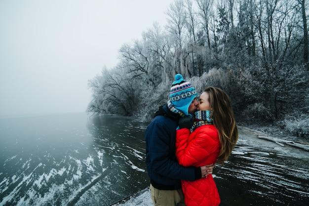 Paare, die mit schneebedeckten hintergrund küssen