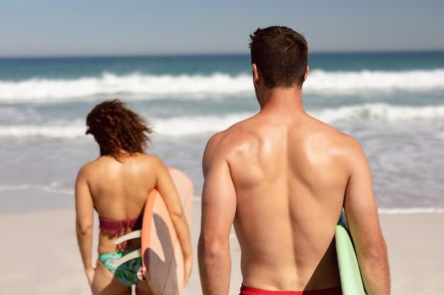 Paare, die mit surfbrett auf strand im sonnenschein gehen