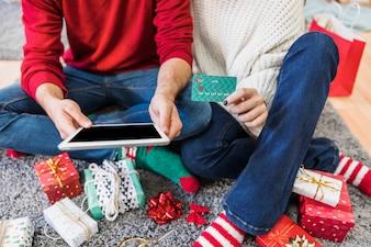 Paare, die mit Tablette und Kreditkarte auf Fußboden sitzen