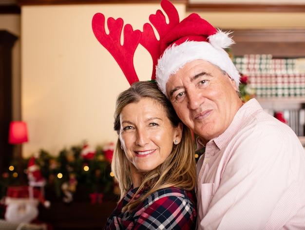 Paare, die mit weihnachten hüte umarmen