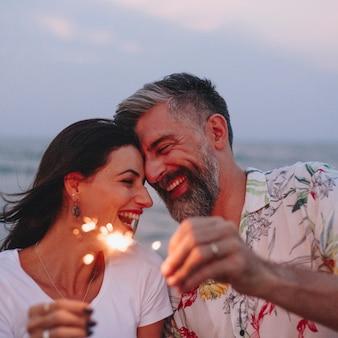 Paare, die mit wunderkerzen am strand feiern