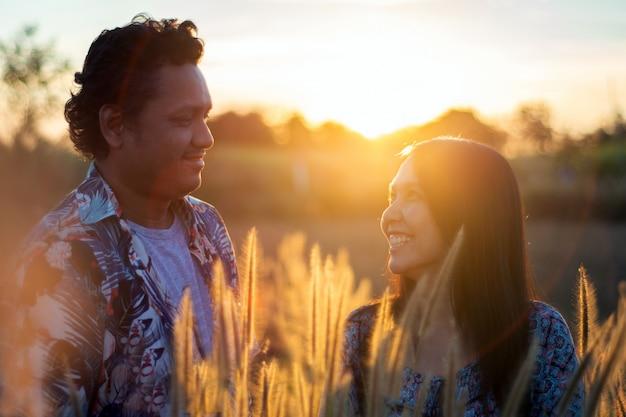 Paare, die natur auf feldgraswiese bei sonnenaufgang genießen