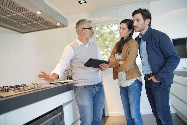 Paare, die neue zeitgenössische küche im ausstellungsraum kaufen