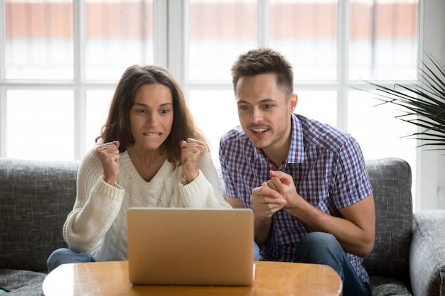 Paare, die online aufpassendes match des unterstützenden teams des laptopschirmes betrachten