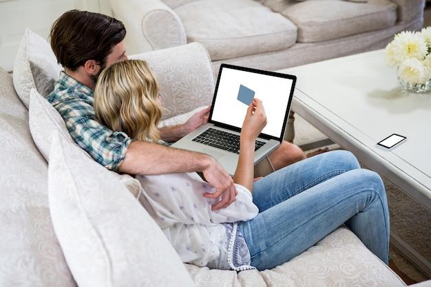 Paare, die online beim sitzen auf sofa kaufen
