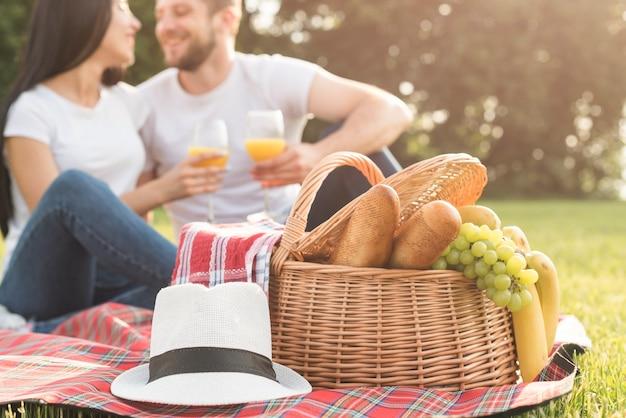 Paare, die orangensaft auf picknickdecke essen