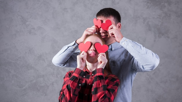 Paare, die papierherzen auf augen halten