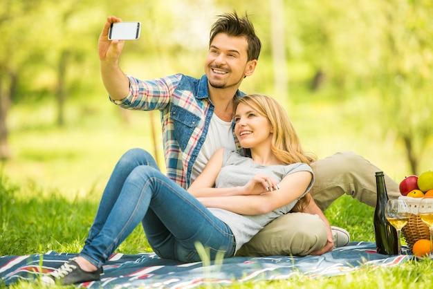 Paare, die picknick im park haben und selfie machen.