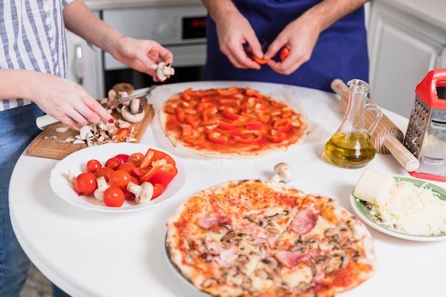 Paare, die pizza mit gemüse und pilzen kochen