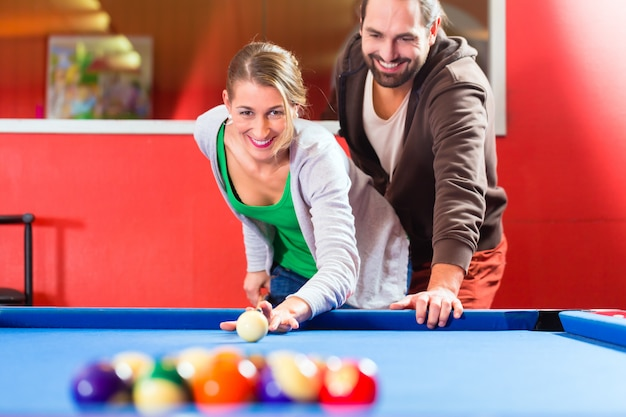 Paare, die poolbillardspiel spielen