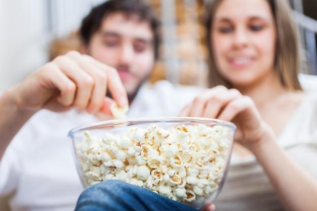 Paare, die popcorn beim aufpassen eines films essen