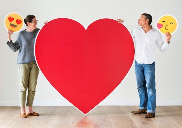 Paare, die rotes herzmodell halten