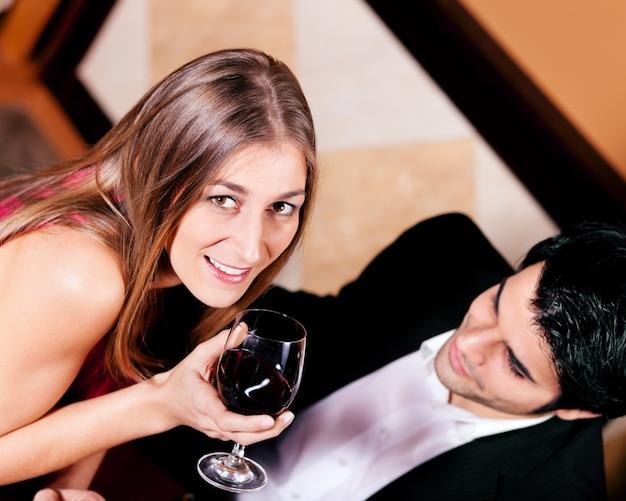 Paare, die rotwein im restaurant essen