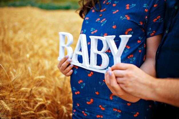 Paare, die schwangeren bauch auf feld umarmen