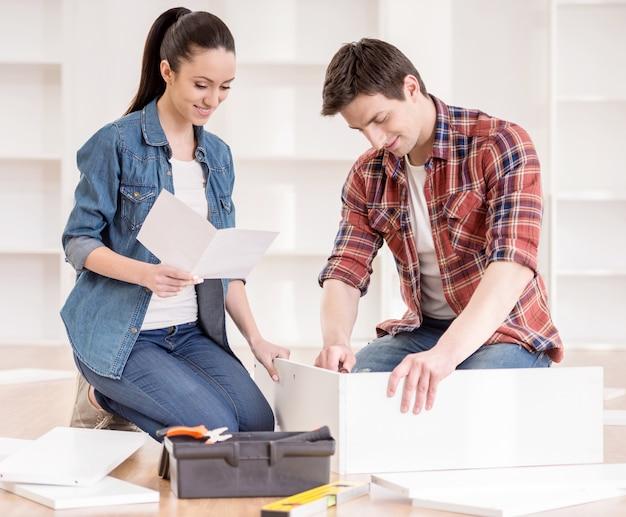Paare, die selbstmontagemöbel zusammenbauen.